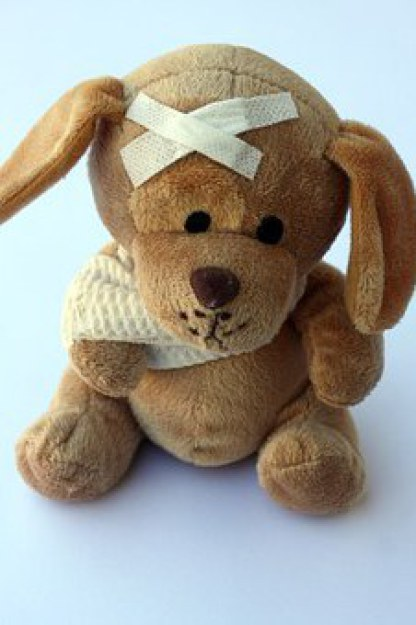 Cute stuffed toy dog with bandage and sling.
